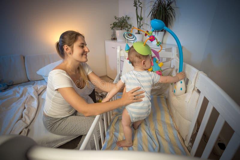Junge Mutter, die ihr Baby steht im Feldbett nachts hält stockfoto