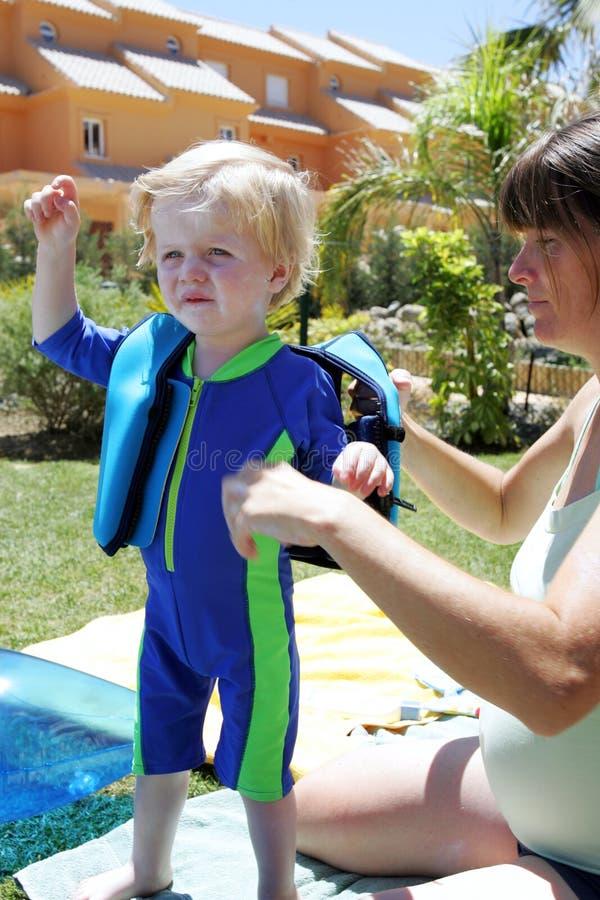 Junge Mutter, die ihr Kind für Schwimmenlektion vorbereitet lizenzfreie stockfotografie