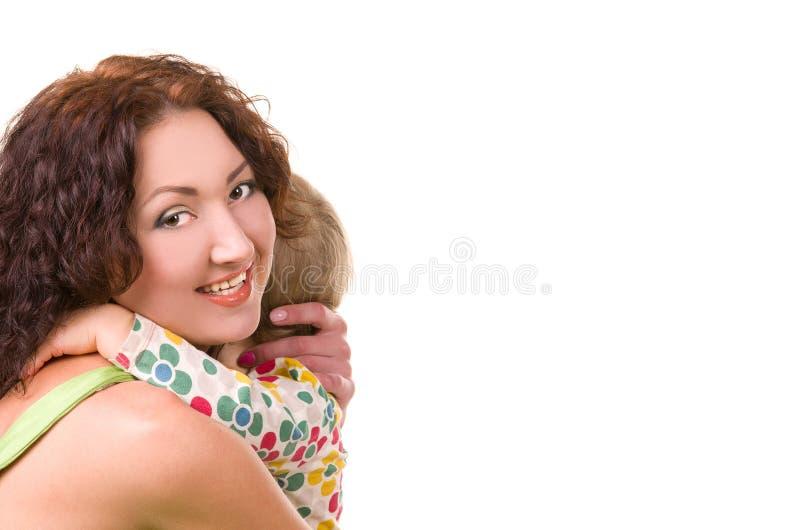 Junge Mutter, die ihr kleines Baby umarmt lizenzfreie stockfotografie