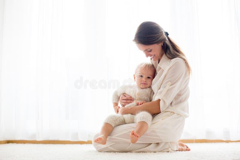 Junge Mutter, die ihr Kleinkindbaby stillt stockfotografie