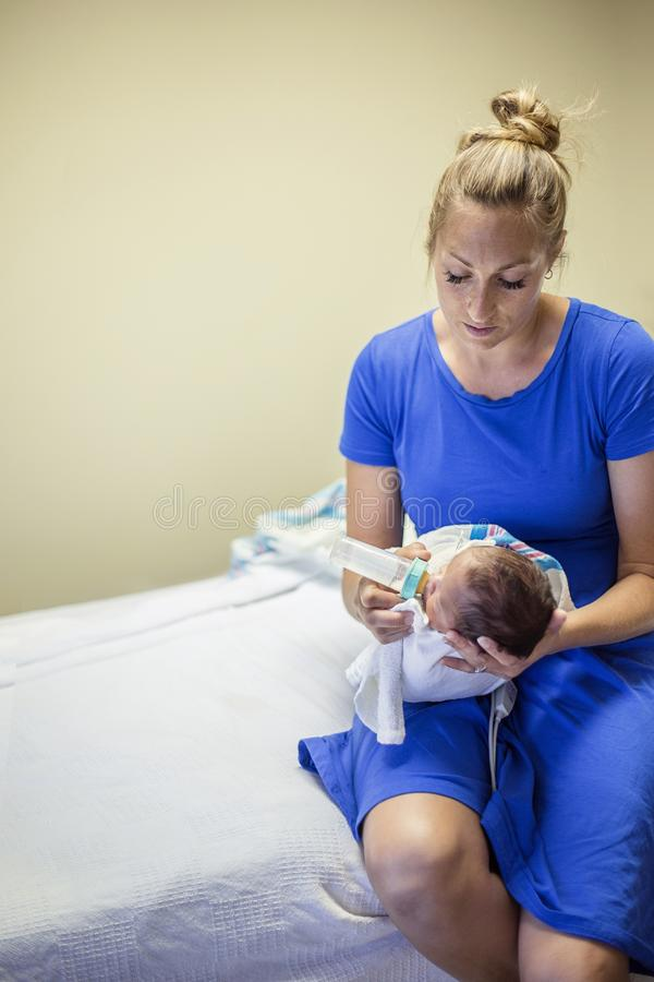 Junge Mutter, die ihr neugeborenes Baby mit der Flasche füttert lizenzfreies stockfoto