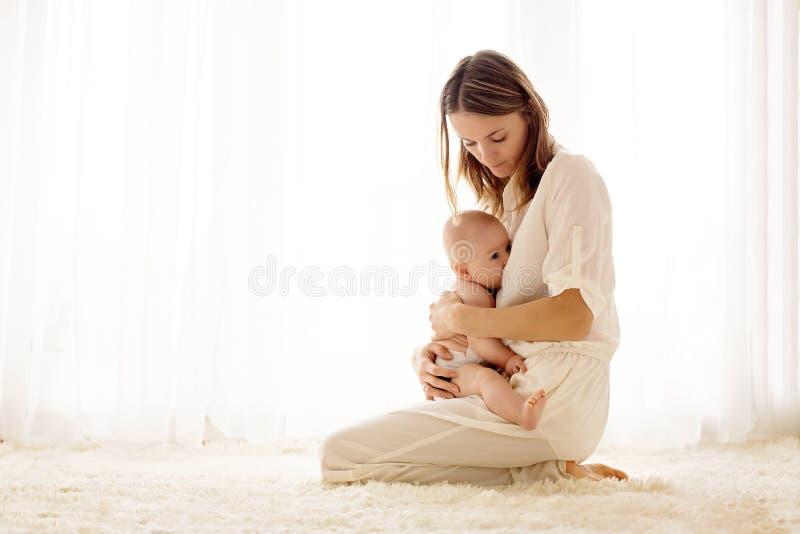 Junge Mutter, die ihr neugeborenes Baby stillt lizenzfreie stockfotos