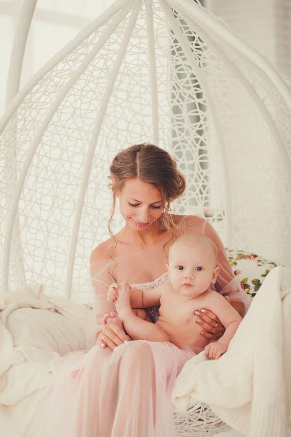 Junge Mutter, die ihr neugeborenes Kind hält stockfotografie
