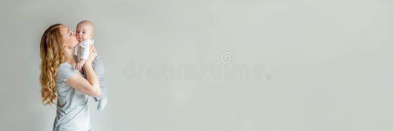 Junge Mutter, die ihr neugeborenes Kind hält fahne lizenzfreies stockbild