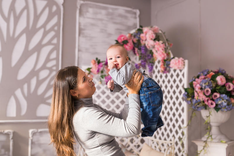 Junge Mutter, die ihr neugeborenes Kind hält Mutterkrankenpflegebaby Frau und neugeborener Junge im Raum Mutter, die mit spielt lizenzfreie stockfotografie
