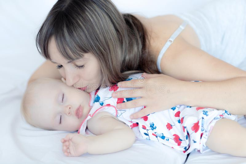 Junge Mutter, die ihr neugeborenes Kind umarmt Mutterkrankenpflegebaby lizenzfreies stockbild