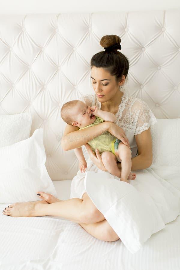 Junge Mutter, die ihre kleine schreiende Tochter hält lizenzfreie stockfotografie