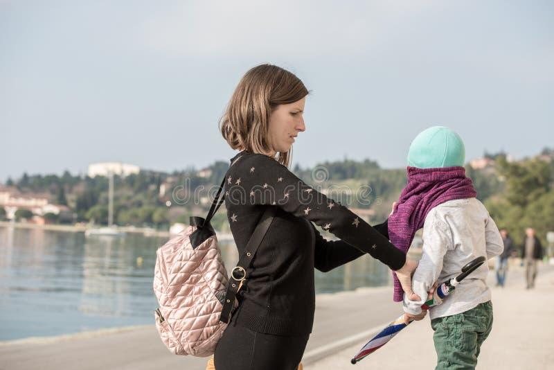 Junge Mutter, die ihren Sohn in einem Pullover kleidet stockfotografie