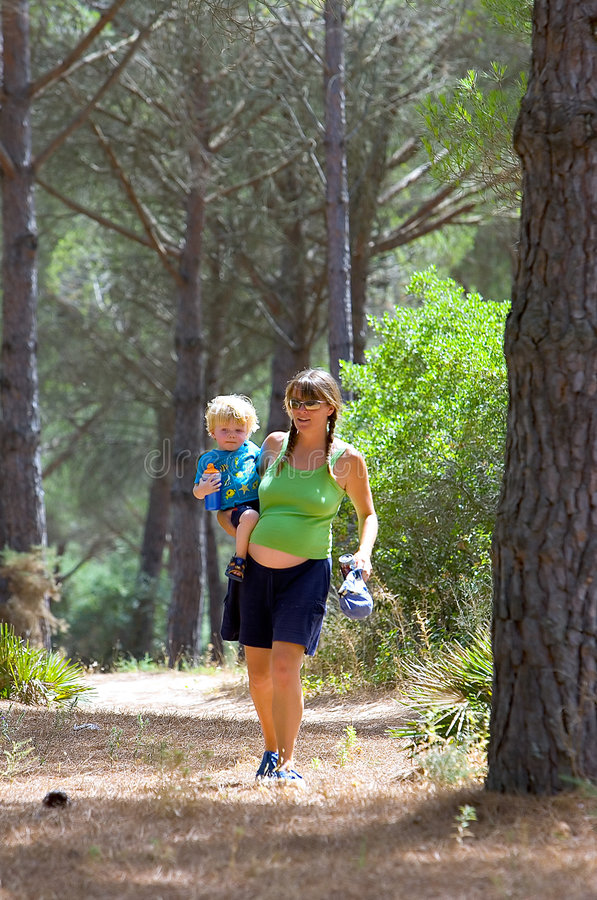 Junge Mutter, die ihren Sohn trägt und durch Holz geht lizenzfreies stockbild