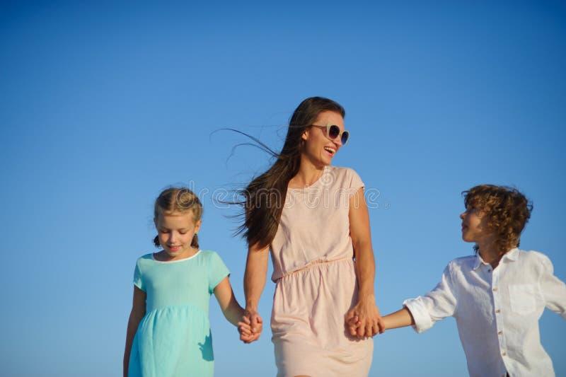 Junge Mutter, die ihren Sohn und Tochter hält lizenzfreie stockfotos