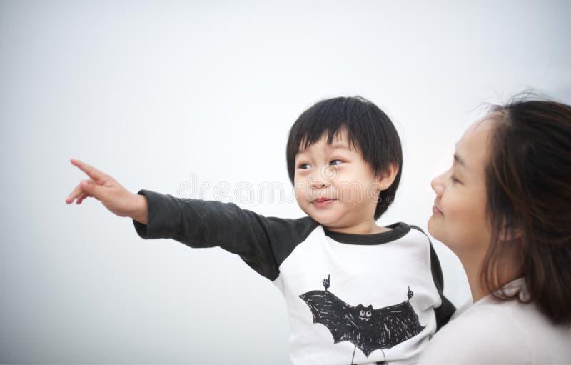 Junge Mutter, die ihren Sohn zeigt Finger hält stockfotografie