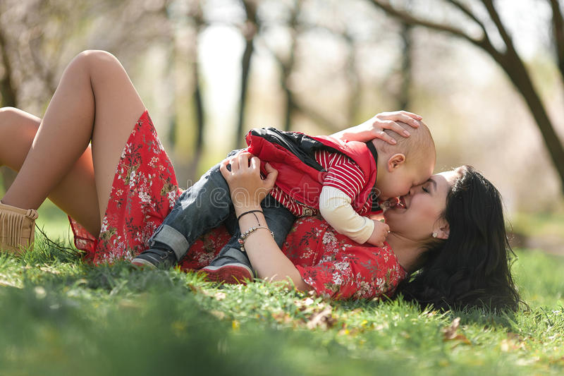 Junge Mutter, die im Frühjahr mit ihrem Baby auf Garten des Wegs spielt stockbilder