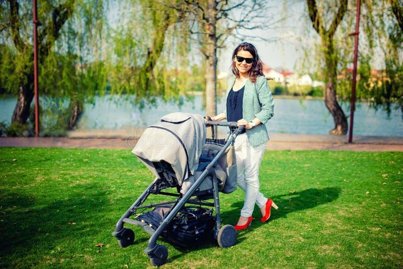 Junge Mutter, die mit Baby im Pram im Park lächelt und geht lizenzfreie stockfotos
