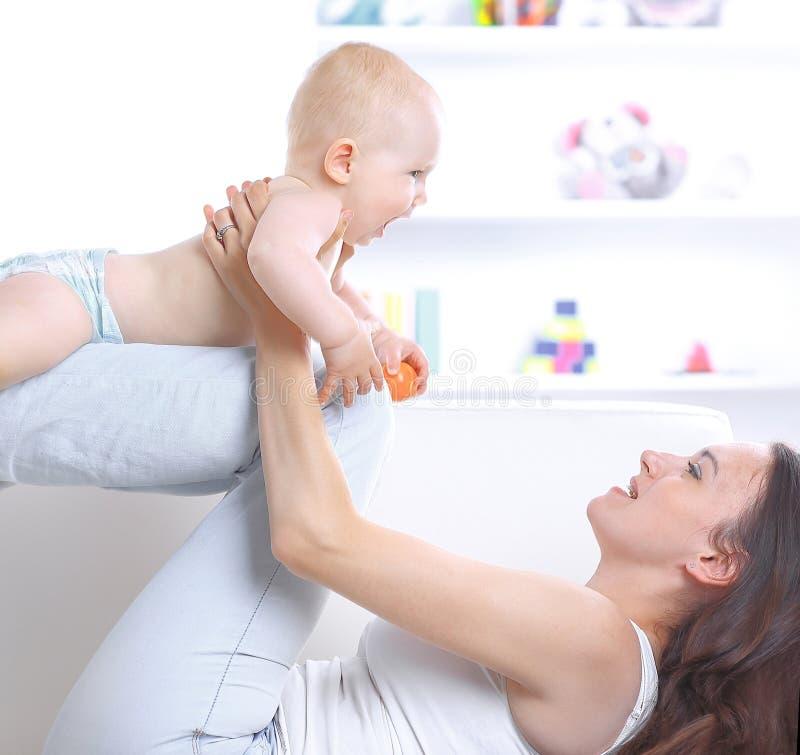 Junge Mutter, die mit einem hübschen Baby auf der Couch spielt stockfotografie