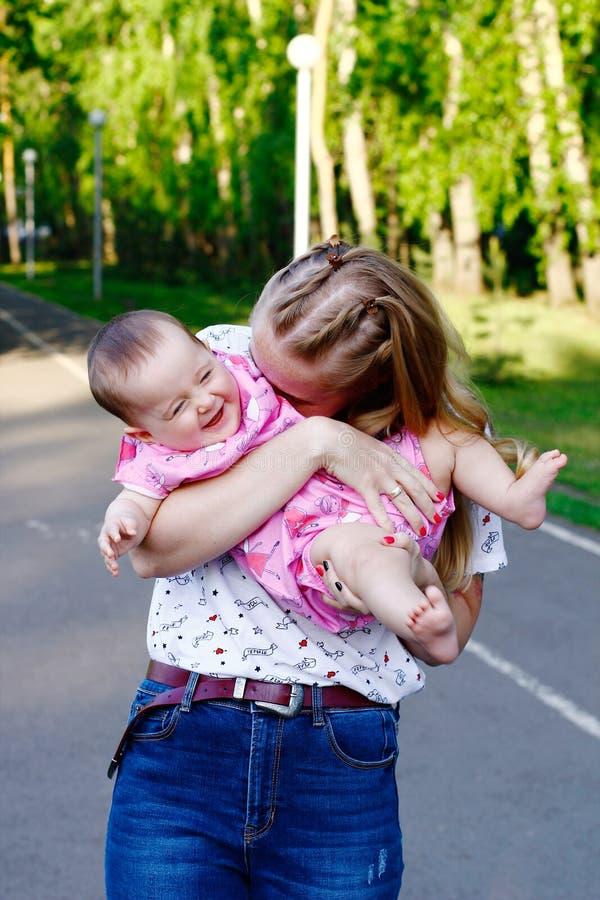 Junge Mutter, die mit ihrem Baby im Park spielt stockfotos
