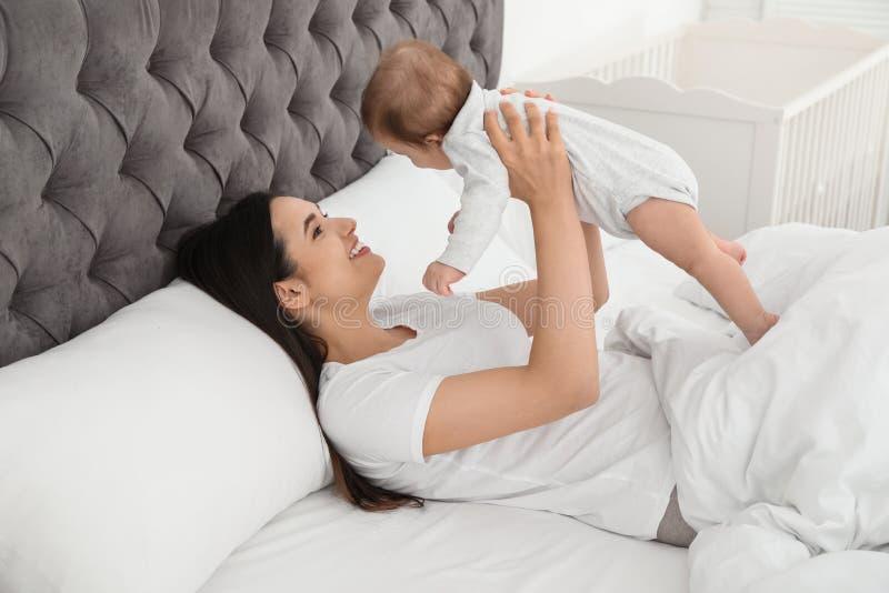Junge Mutter, die mit ihrem netten Baby auf Bett spielt stockfotografie
