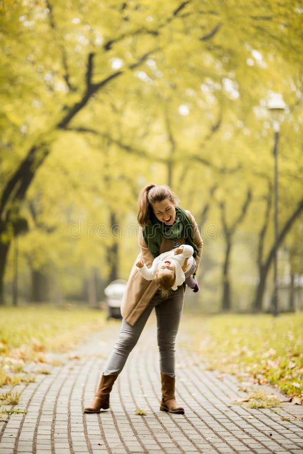 Junge Mutter, die mit ihrer Tochter im Herbstpark spielt stockfotografie