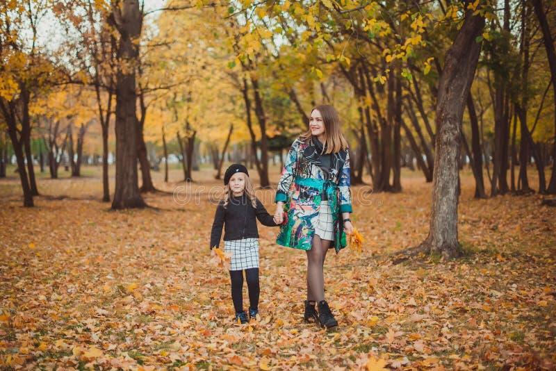 Junge Mutter, die mit ihrer Tochter im Herbstpark spielt lizenzfreies stockbild