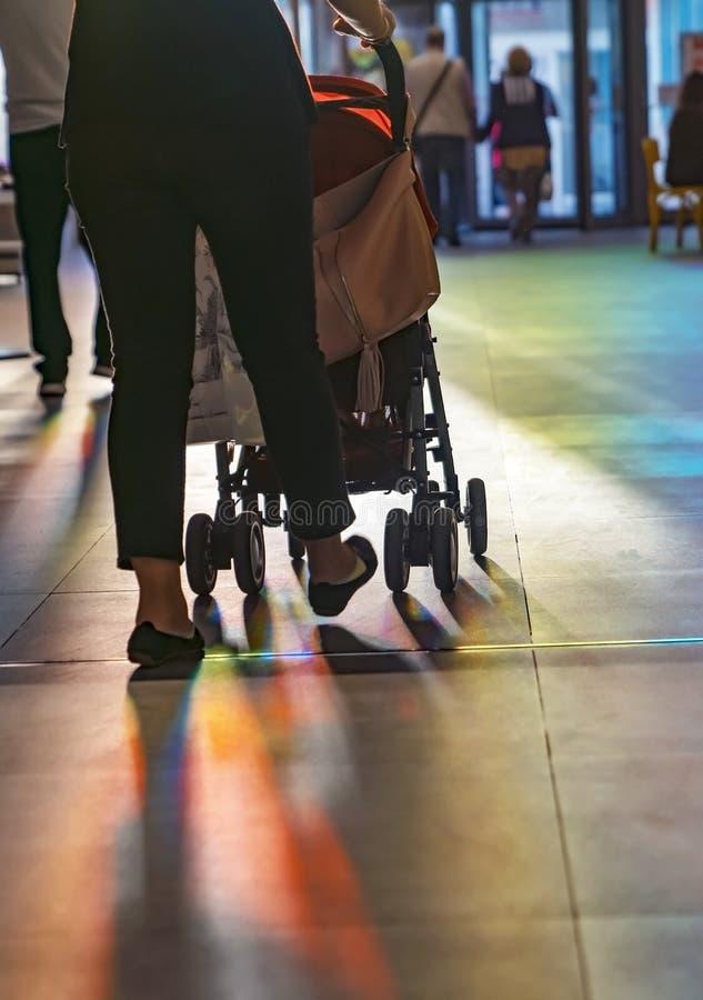Junge Mutter, die mit Kinderwagen im Einkaufszentrum geht stockbild