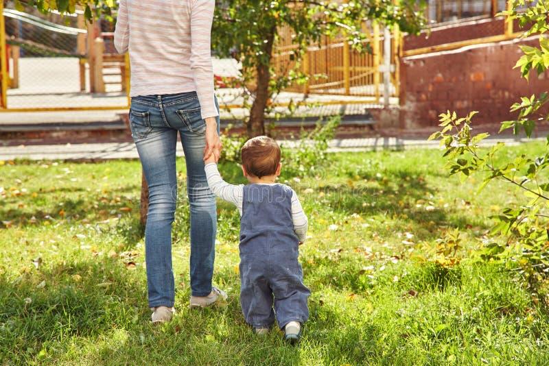 Junge Mutter, die mit Schätzchen spielt Mutter und Sohn, die in einen Park gehen stockfotografie