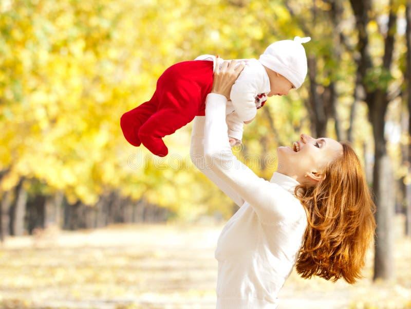 Junge Mutter, die mit Tochter im Herbstpark spielt lizenzfreies stockbild