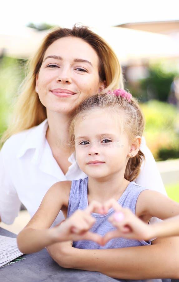 Junge Mutter, die mit weniger Tochter zeigt Herzgeste sitzt lizenzfreie stockbilder