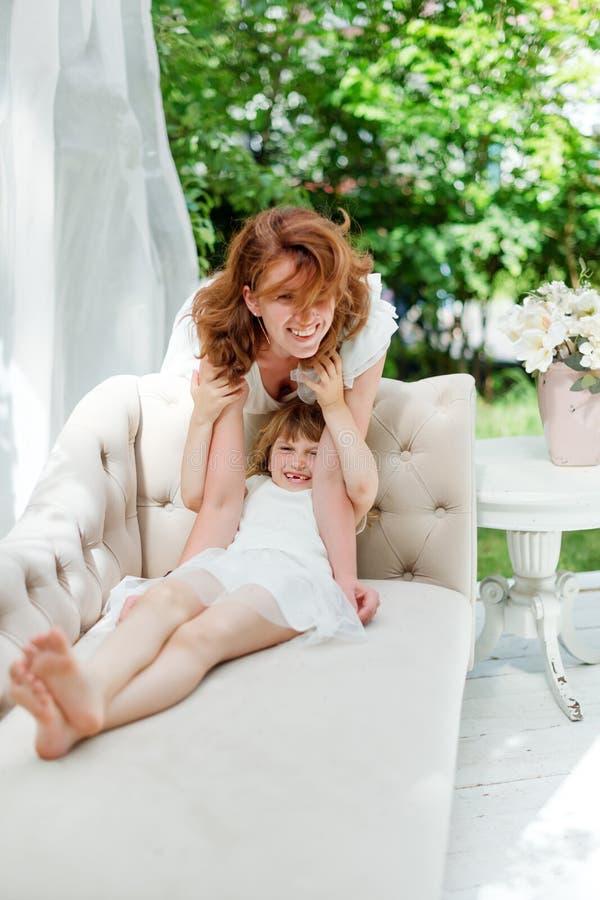 Junge Mutter, die Spaß mit ihrer kleinen Tochter im grünen Sommerpark spielt und hat Familienglück, Kindheitskonzept stockbild