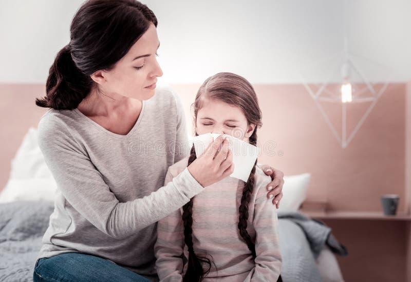 Junge Mutter, die um ihrem kranken Kind sich kümmert stockfotografie