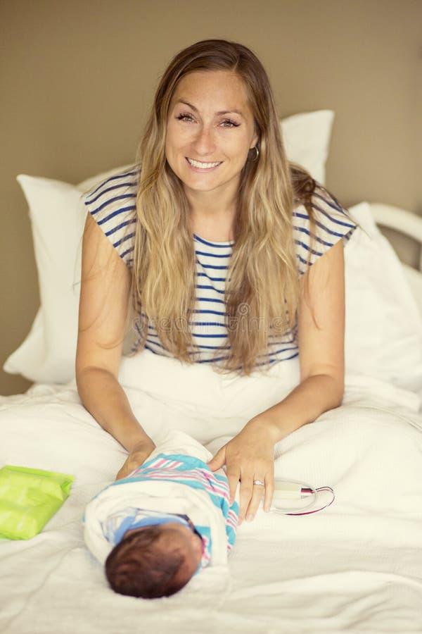 Junge Mutter in einem Krankenhausbett mit ihrem neugeborenen Baby stockfoto