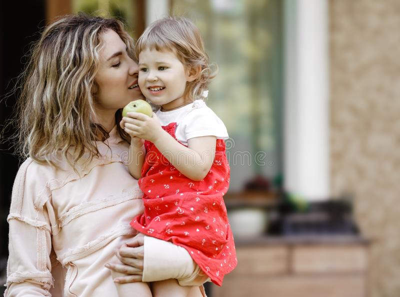 Junge Mutter hält ihre wenige Tochter auf ihren Händen und küsst ihre süße Backe im Garten an einem warmen Sommertag stockfoto
