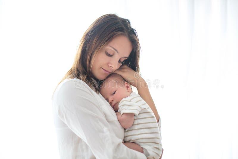 Junge Mutter, ihr neugeborenes Baby halten stockbild