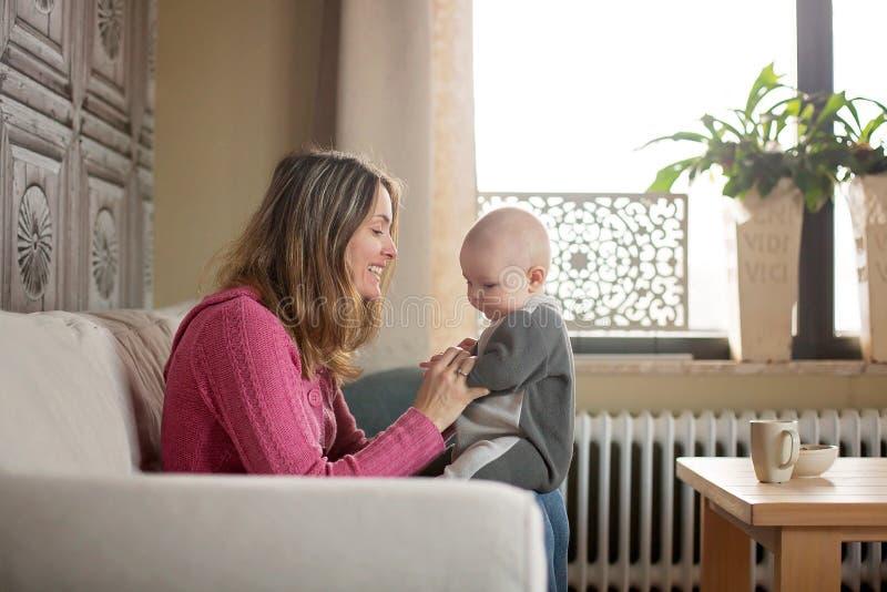 Junge Mutter, ihren Kleinkindjungen halten und zu Hause stillen ihn lizenzfreies stockbild