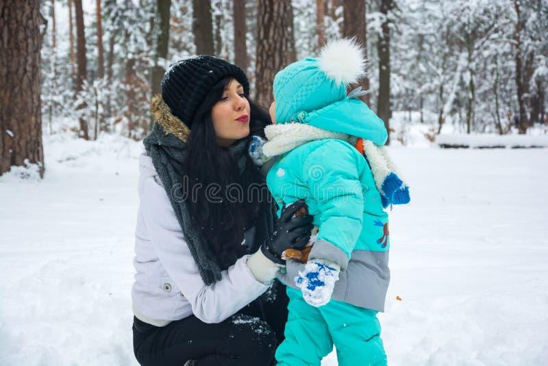 Junge Mutter küsst ihr Baby im Winterpark stockfotografie