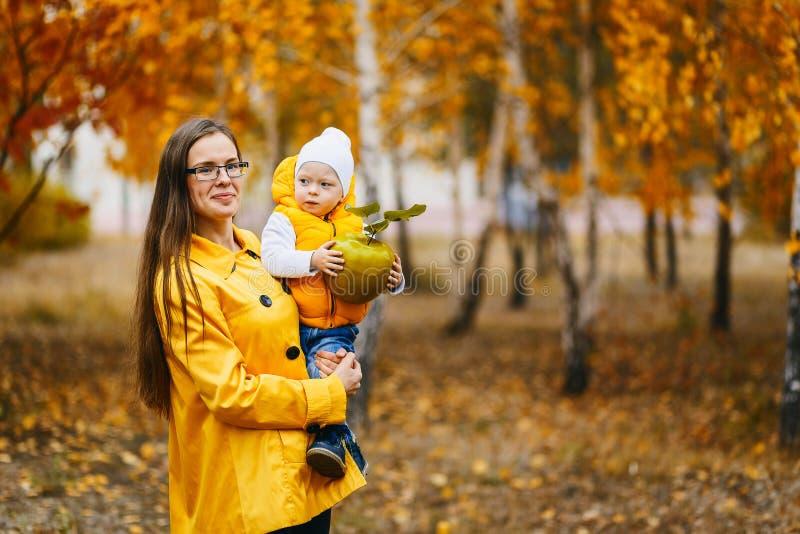 Junge Mutter mit Baby zu Händen von Herbst stockfoto