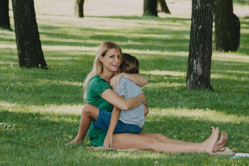 Junge Mutter mit dem langen weißen Haar umarmt Sohn auf Gras lizenzfreie stockfotografie