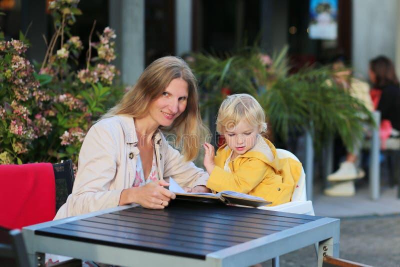 Junge Mutter mit der kleinen Tochter, die Mahlzeit im Freiencafé hat stockfotos