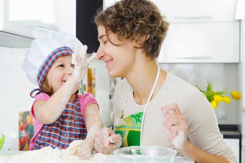 Junge Mutter mit der kleinen Tochter, die Plätzchen zubereitet stockbild