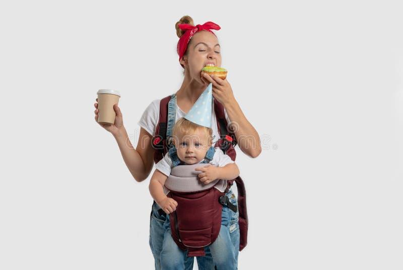 Junge Mutter mit einem Baby in einem Rucksack verschlingt Donut mit Kaffee am Tag der Geburt des Sohns, lokalisiert über Weiß stockfotografie