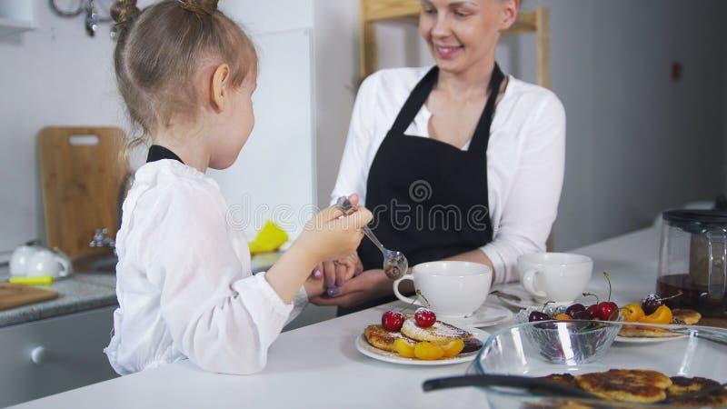 Junge Mutter mit ihrem Kind, das zusammen selbst gemachte Pfannkuchen kocht stockfotografie