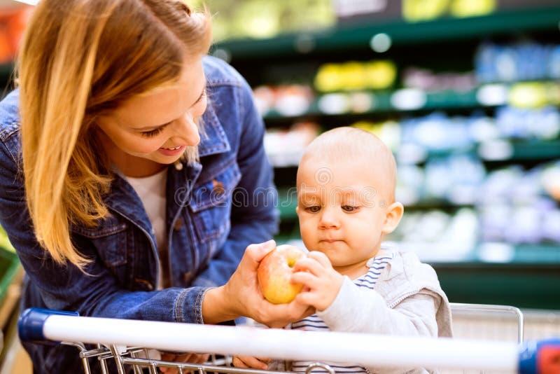 Junge Mutter mit ihrem kleinen Baby am Supermarkt lizenzfreies stockbild