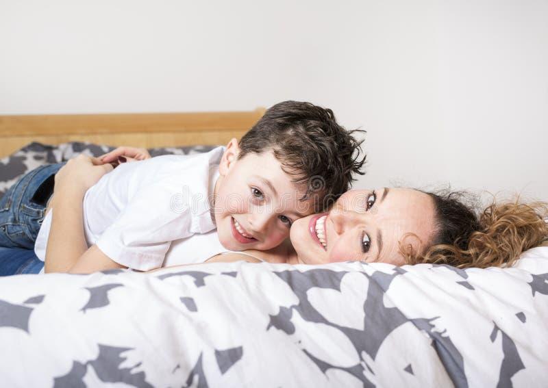 Junge Mutter mit ihrem Sohn, der sich am Wochenende im Bett zusammen entspannt und spielt lizenzfreies stockfoto