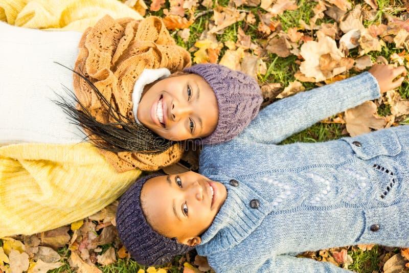 Junge Mutter mit ihrer Tochter, die in den Blättern liegt lizenzfreie stockfotografie