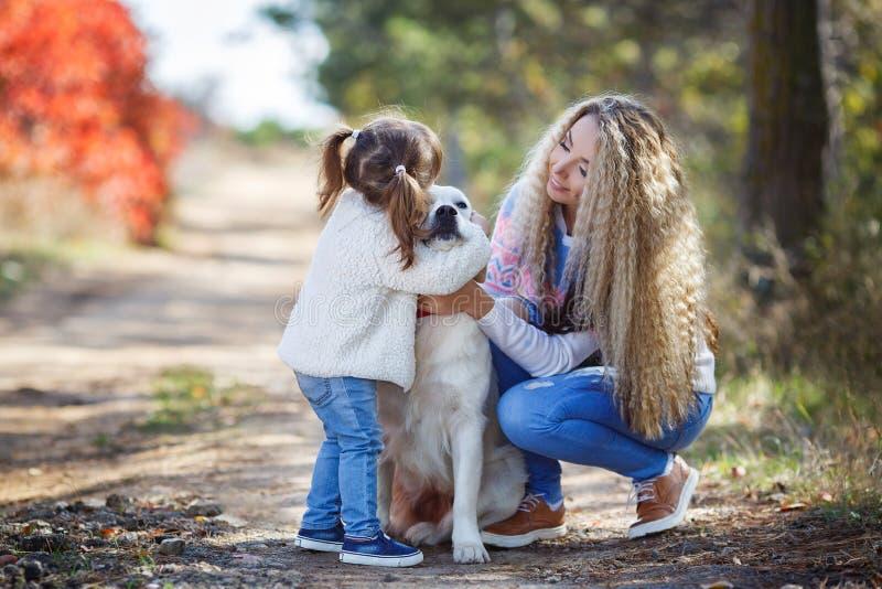 Junge Mutter mit kleinem Mädchen und Hund auf Weg im Herbst parken lizenzfreies stockfoto