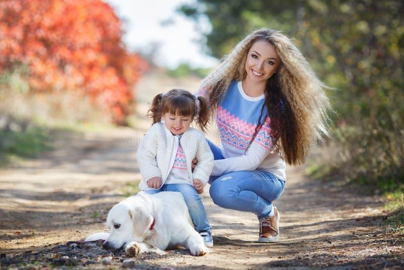 Junge Mutter mit kleinem Mädchen und Hund auf Weg im Herbst parken stockfotos