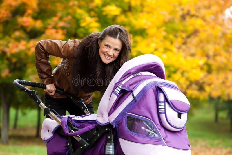 Junge Mutter mit Schätzchen im Spaziergänger geht in Park stockfoto