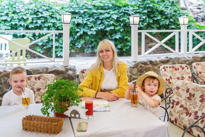 Junge Mutter mit zwei Kindern, welche die Mahlzeit sitzt am Café genießen lizenzfreie stockfotografie