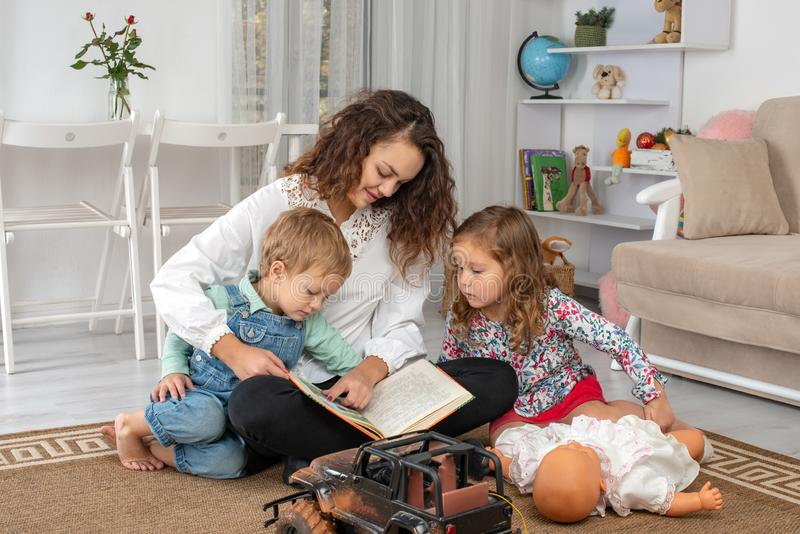 Junge Mutter oder Kindermädchen mit kleinen Kindern, ein Junge und ein Mädchen, sitzen lizenzfreie stockfotografie