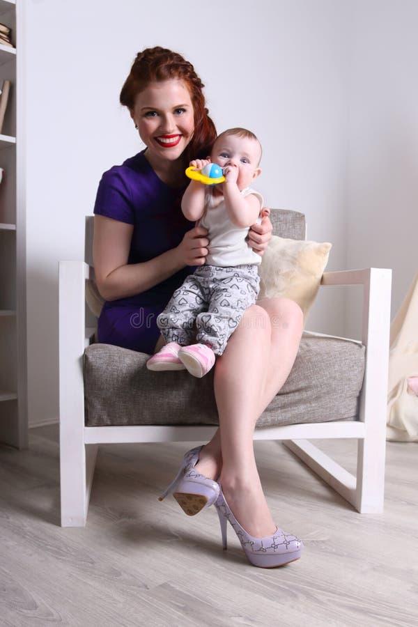 Junge Mutter sitzt mit ihrem kleinen Baby auf Lehnsessel lizenzfreie stockfotos