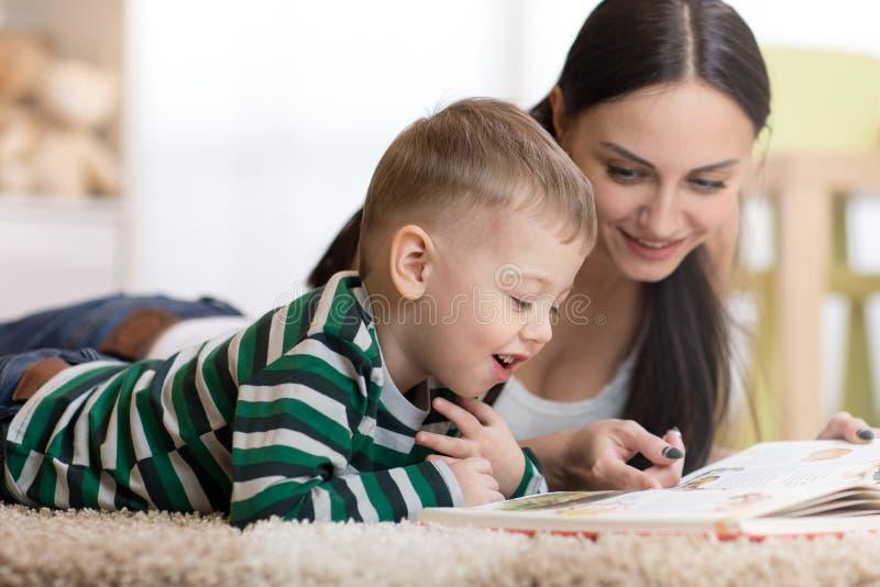 Junge Mutter und ihr Kindersohn liegen auf dem Boden- und Lesebuch lizenzfreies stockbild