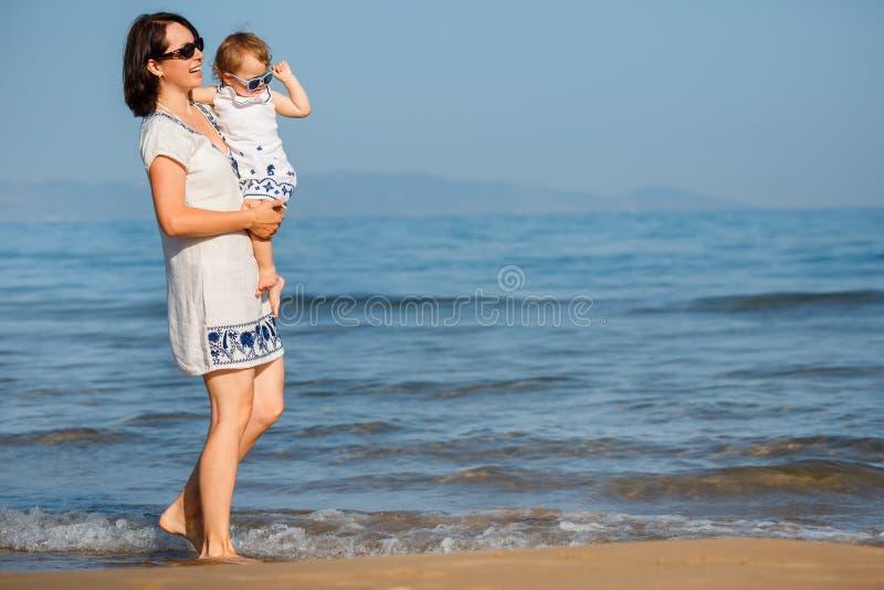 Junge Mutter und ihr nettes kleines Baby, die auf einem schönen tropischen Strand spielt lizenzfreies stockfoto